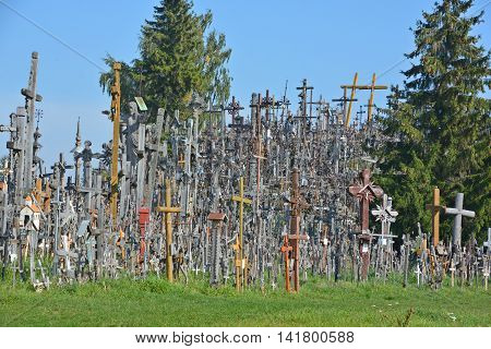 SIAULIAI, LITHUANIA SEPTEMBER 15 2015: Flag of Lithuania and view of hill of crosses with over four hundred thousand crosses and crucifix, which is thought tradition of putting a cross traces to 1800s