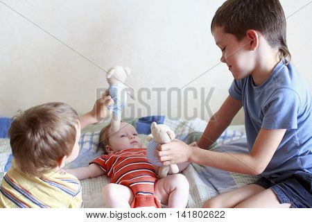 two elder brothers are playing with the newborn. cute boys lovingly playing with their baby sister. the concept of love and friendship between older and younger siblings