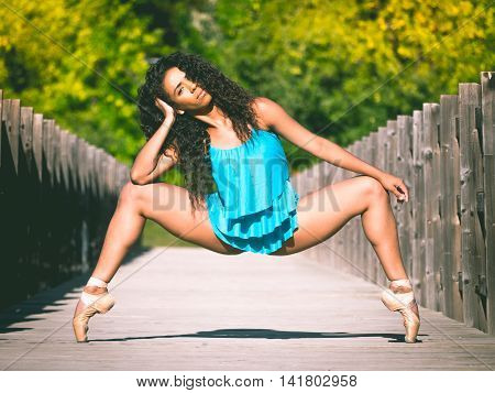 Latin dancer woman in second position and grand plie on a bridge in a park outdoors