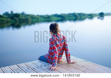 boy on the pier looking at the water. boy in a plaid shirt sitting on a wooden pier. view from the back. on the river calm and silence. away rides powerboat