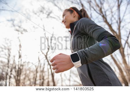 Runner wearing smartwatch on wrist closeup. Heart rate monitor watch on Young fitness woman running working out cardio in autumn or winter outdoors on forest trail fall wearing cold weather jacket.