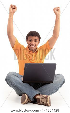 Happy african american man working on laptop.
