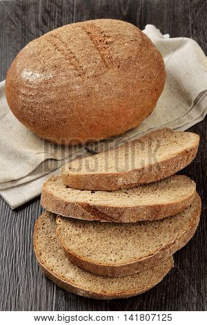 A loaf of rye-wheat bran bread with slices on wooden background