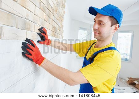wall facing work with brick by professional bricklayer worker