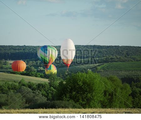 Balloons fly over the green fields, hills in summer
