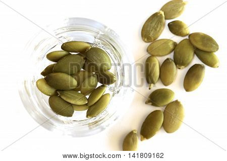 Some green raw pepitas in a glass bowl.