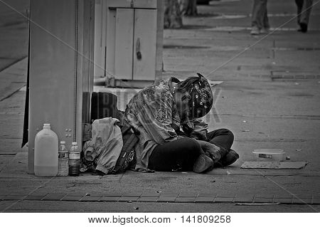 A homeless person looking hopeless on the side of the street