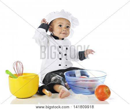 An adorable baby boy messed up with flour in his chef's outfit.  Bowls of apples and cooking utensiles are nearby.  On a white background.