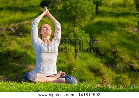 Meditation and relaxation yoga outdoors - young woman meditating and relaxing in Padmasana Lotus Pose) on green grass in forest