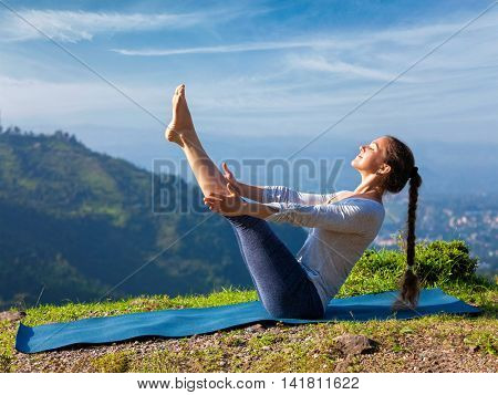 Yoga outdoors - young sporty fit woman doing Ashtanga Vinyasa Yoga asana Navasana - boat pose  - in Himalayas mountains in the morning  Himachal Pradesh, India