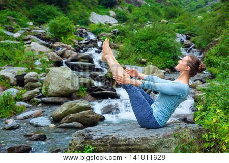 Yoga outdoors - young sporty fit woman doing Ashtanga Vinyasa Yoga asana Navasana - boat pose  - in Himalayas at tropical waterfall. Himachal Pradesh, India