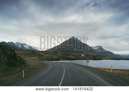 Landscape with road and mountains. Cloudy summer day. Southeast Iceland, Europe. Art processing of photographs, color toning