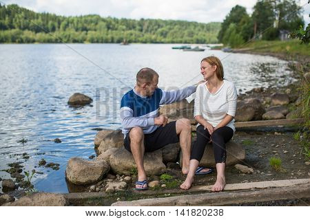 Young couple sitting on the rocks by the river. Honeymoon.