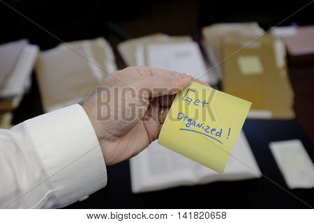 Hand holding sticky note Get Organized business clean