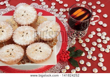 Christmas mince pie cakes with mulled wine, holly and silver chocolate button decorations on red background.
