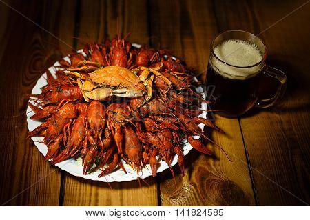 Dark foamy beer in glass mug and large dish with boiled crawfish and crab on a wooden table. Beer Party. Beer plate. Beer Day. Oktoberfest. Beer tradition.