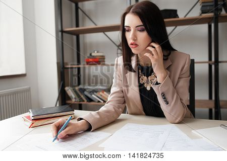 Female accountant checking financial documents, counting income for tax form completion. Internal Revenue Service inspector checking financial document. Planning budget, audit, insurance concept