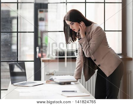 Attractive business woman standing leaning on desk in office, reading her notebook.