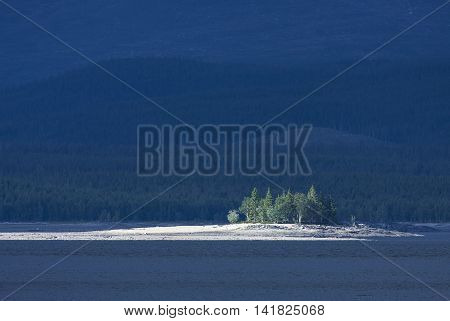 A small island in bright sunshine in a lake. Forests and ridges in the background. Rural countryside.