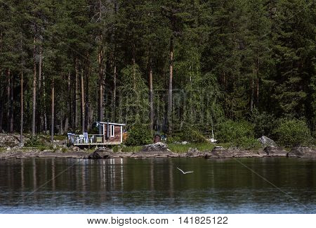RURAL COUNTY, SWEDEN ON JULY 09. View of a cabin, cottage and lake surrounded by forests on July 09, 2016 in Rural County, Sweden. Shore, porch and sunshine. Editorial use.