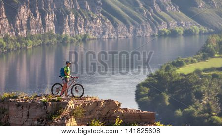 Young woman athlete standing on top of a mountain with bicycle and enjoying valley and river view