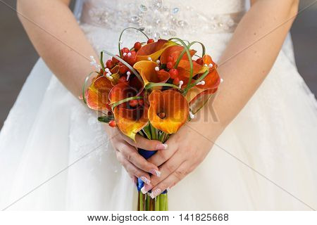 beautiful wedding bouquet of orange Calla lilies in the hands of the bride