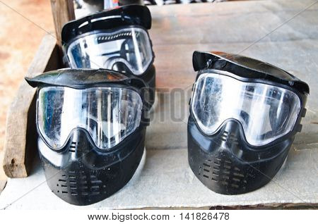 Paintball mask on rustic wooden background ready to play