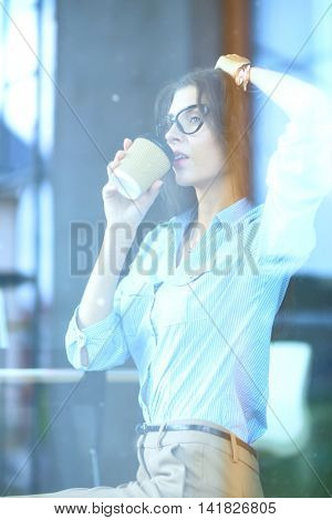 Businesswoman drinking from mug while working on laptop at the office