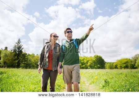 travel, hiking, backpacking, tourism and people concept - happy couple with backpacks walking along country road outdoors and pointing finger to something
