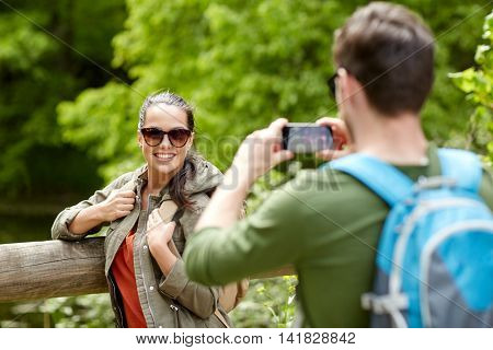 travel, hiking, backpacking, tourism and people concept - smiling couple with backpacks taking picture by smartphone in nature