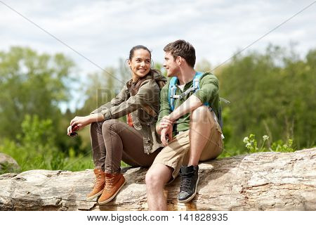 travel, hiking, backpacking, tourism and people concept - smiling couple with backpacks resting and talking in nature