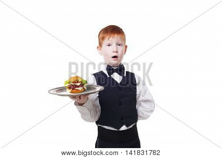 Little surprised waiter stands with tray serving hamburger. Redhead child boy in suit plays restaurant servant, gives burger isolated at white background