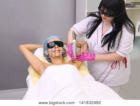 Blonde woman having underarm Laser hair removal epilation. Laser treatment in cosmetic salon.