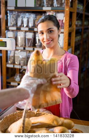 Staff giving packet bread to woman in supermarket