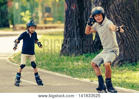 Grandfather Teaching Grandson Roller Skating In The Park