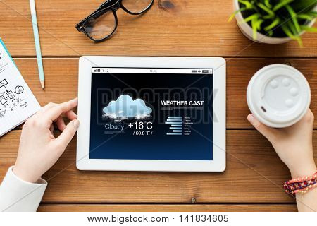technology, people and forecast concept - close up of woman with weather cast on tablet pc computer screen and coffee on wooden table
