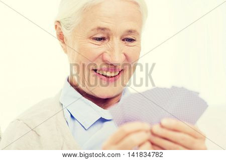 age, game, gamble, poker and people concept - happy smiling senior woman playing cards at home