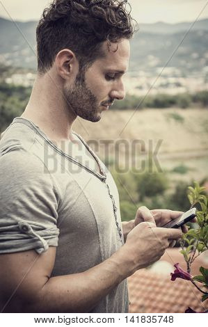 Handsome trendy man using cell phone to type text message outdoor. Side view