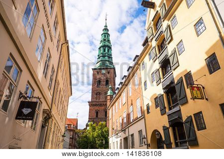 Copenhagen Denmark - July 20 2015: Admiral Garden street with the bell tower of S. Nicholai church in the background