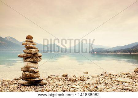 Balanced Stone Pyramide On Shore, Blue Water Of Mountain Lake.