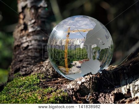 Ball Sphere in the woods on moss. Reflection - the city crane building metropolis. The concept of urban ecology construction nature protection