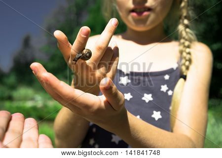 Beautiful blonde girl holds a snail on the hand