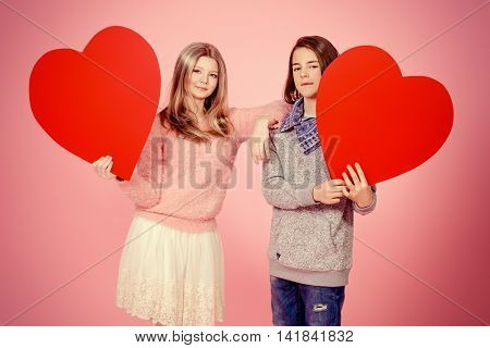 Happy teenage boy and girl holding red hearts over pink background. Friendship. First love. Valentine's Day.