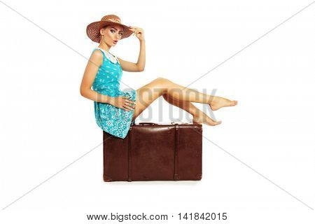 Beautiful sexy tanned barefoot pin-up girl in stylish dress and hat sitting on big vintage bag over white background