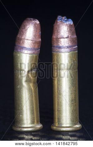 Two rimfire round that have been damaged during feeding