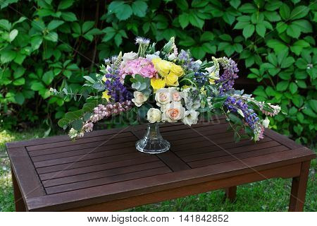 Beautiful flower composition outdoors. Wedding floristic decoration at wooden table, bouquet of colorful wildflowers and white roses in glass vase at green leaves background