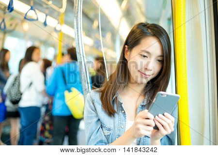 Woman sending sms on cellphone in train