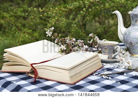 Open diary with cup of tea and flowers of cherry tree on checked tablecloth in the spring garden