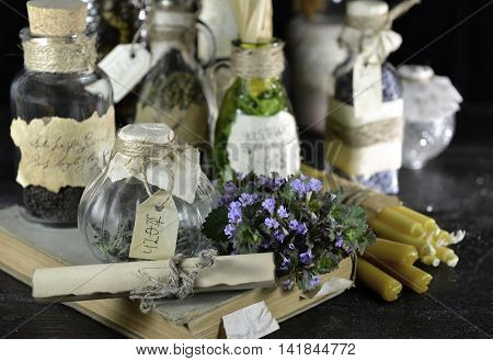 Still life with bottles, candles and healing herbs. Halloween or homeopathic image. Signs on labels are not foreign text, these letters are imaginary, fictional symbols.