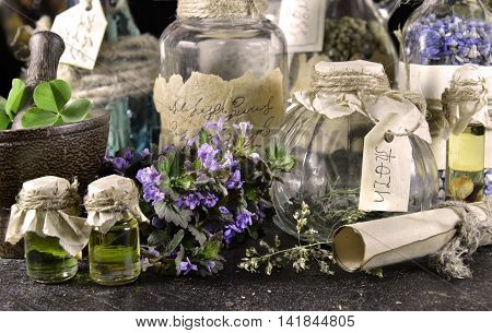 Witch bottles with healing herbs. Halloween or homeopathic image desaturated. Signs on labels are not foreign text, these letters are imaginary, fictional symbols.